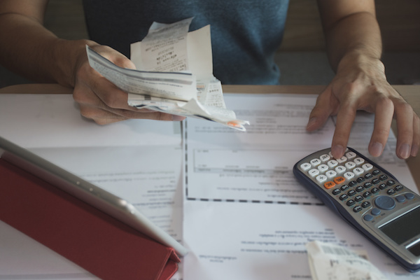 man using calculator for calculate expenses accounts
